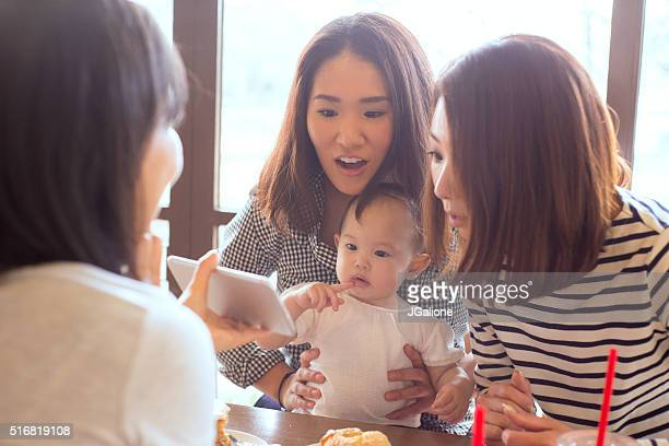 Three friends and a baby in a cafe together