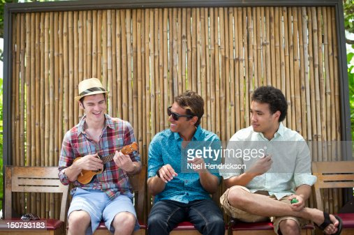 Three friends at a cafe playing instruments : Photo