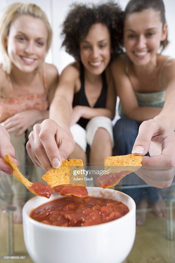 Three friends eating tortillas with dip (focus on tortillas and dip)