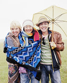 Three friends embracing under umbrella, smiling, portrait