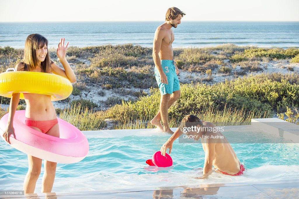 Three friends enjoying at a swimming pool on the beach