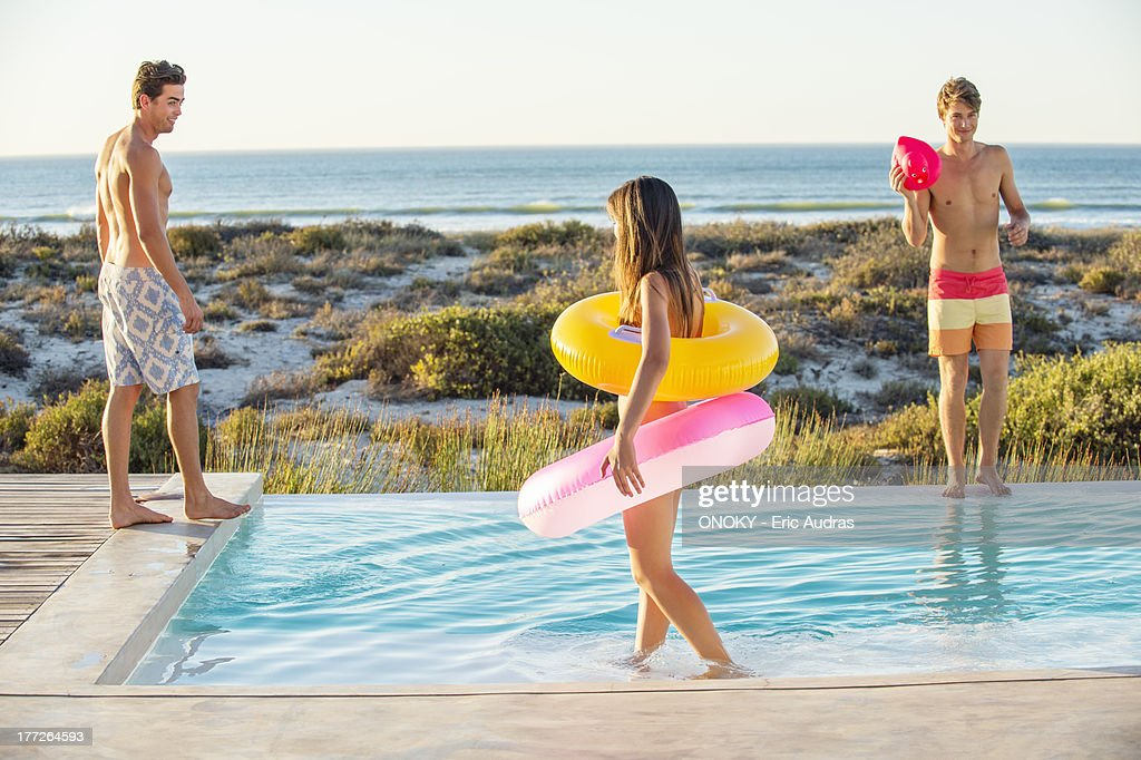 Three friends enjoying at a swimming pool on the beach : Stock Photo
