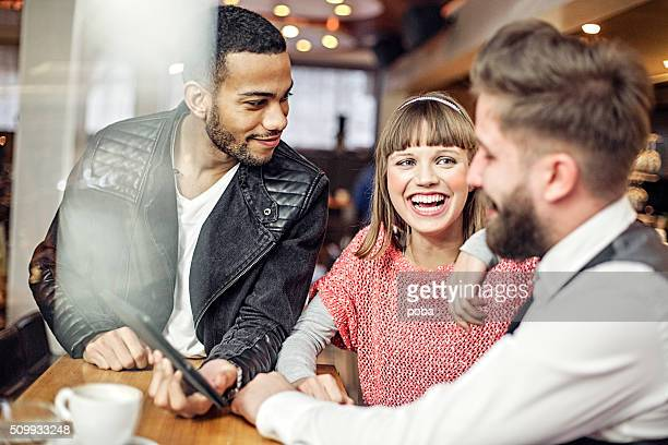 Three friends in a bar with drinks using digital tablet