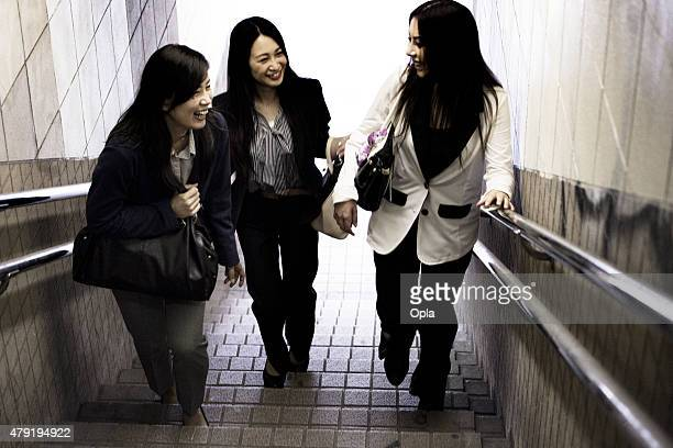 Three Friends Laughing and Talking on Stairs