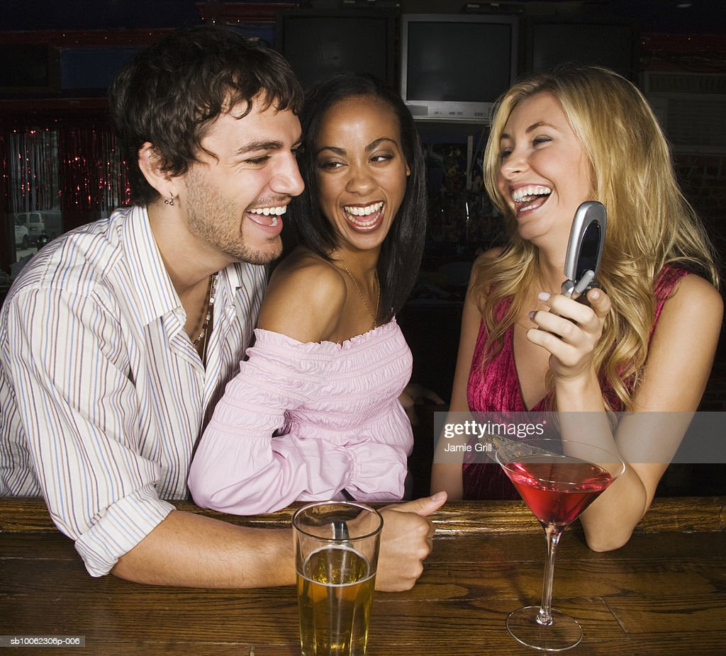 Three friends laughing at bar area, woman holding mobile phone : Stock Photo