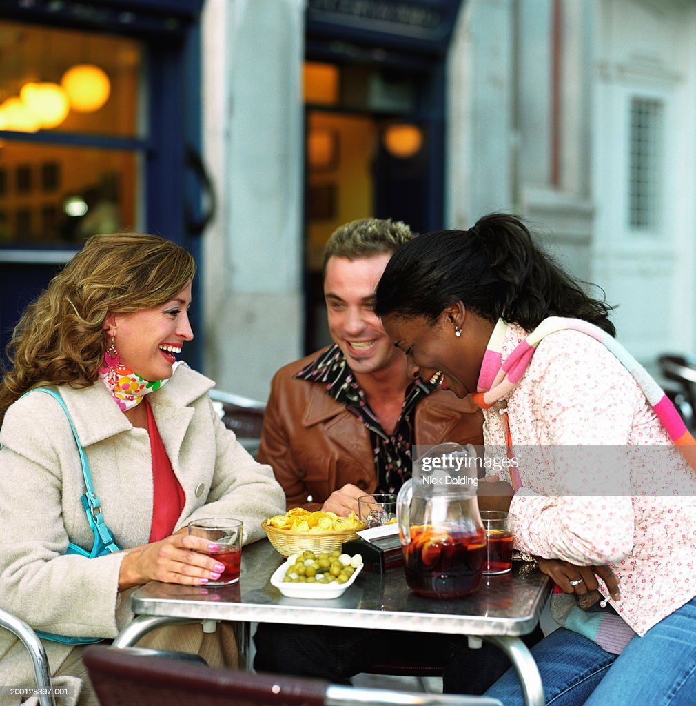 Three friends laughing at table of outdoor cafe : Stock Photo