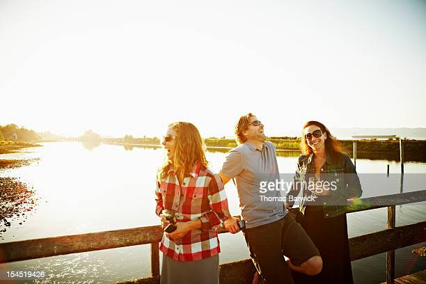 Three friends laughing on dock at sunset