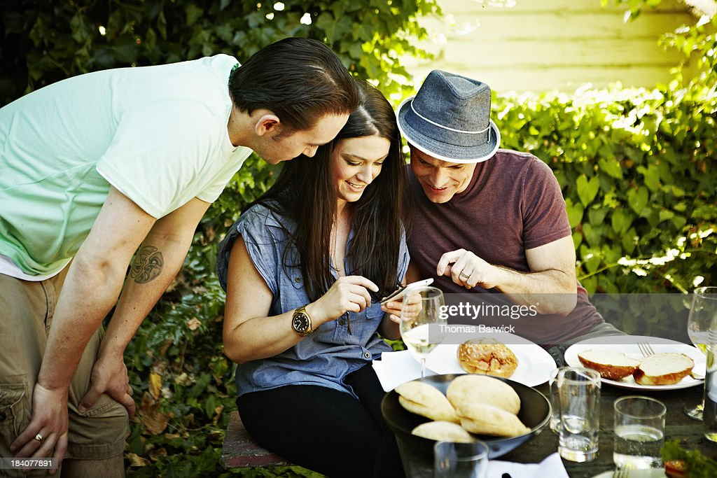 Three friends looking at smart phone together : Stock Photo