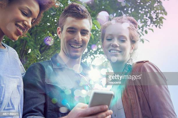 Three friends looking at smartphone with lights coming out of it
