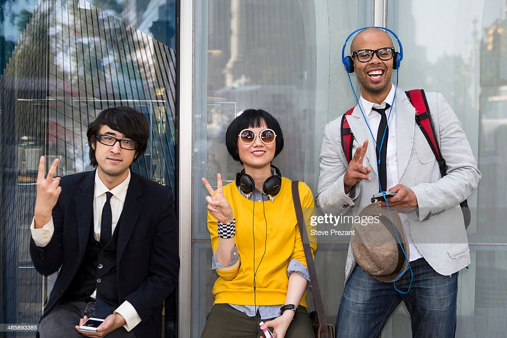 Three friends making victory sign : Stock Photo
