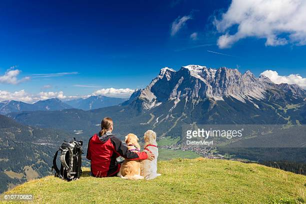 Three friends, man puts arm to his dogs at Zugspitze