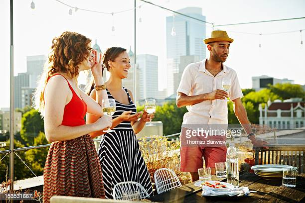 Three friends on rooftop deck drinking wine