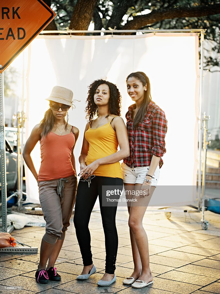 Three friends on street against white background : Stock Photo