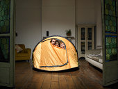 Three friends peering from tent in living room
