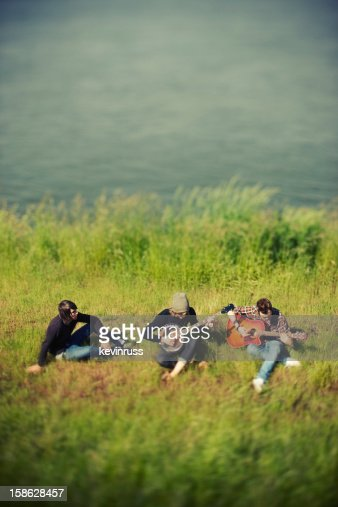 Three Friends Playing Instruments in the Grass