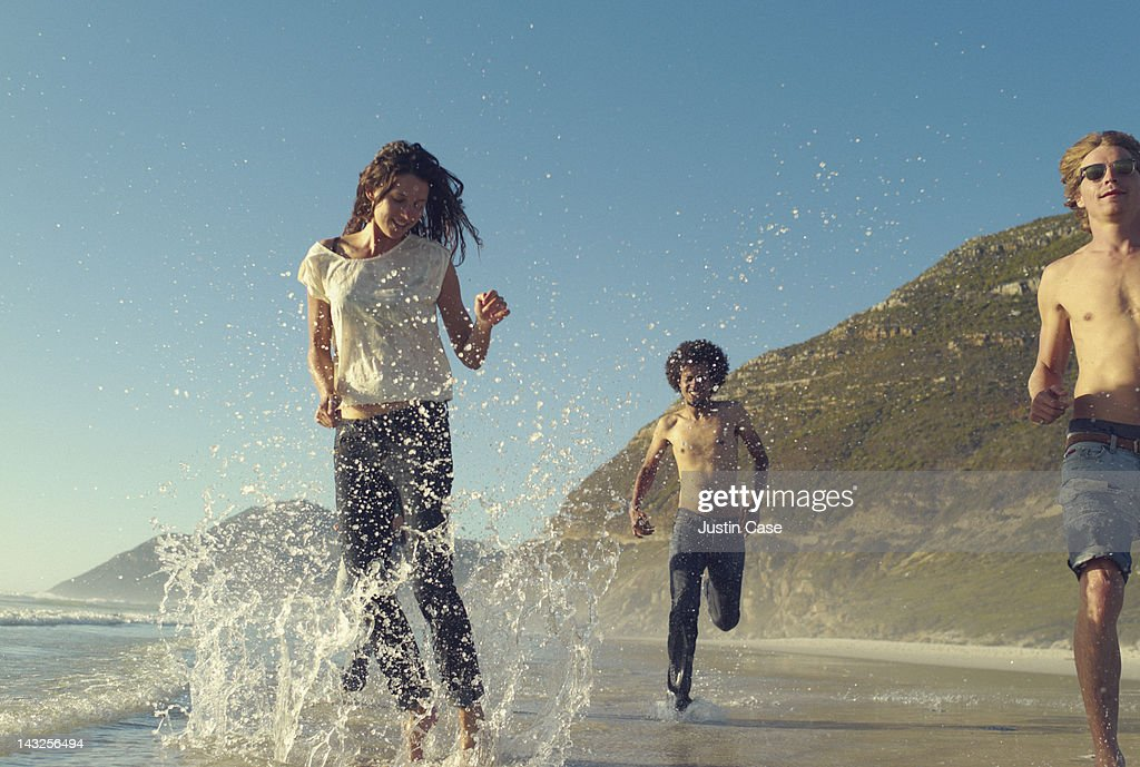 Three friends playing on the beach : Stock Photo