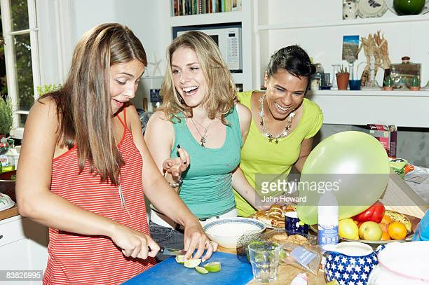 Three friends preparing food for party