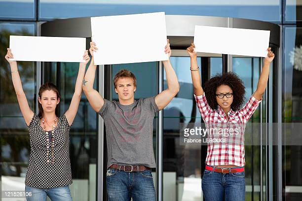 Three friends protesting with blank placards