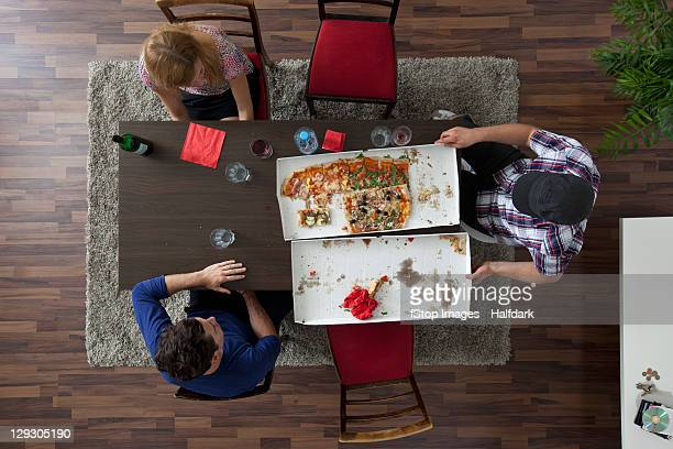 Three friends relaxing around a table after eating pizza, overhead view