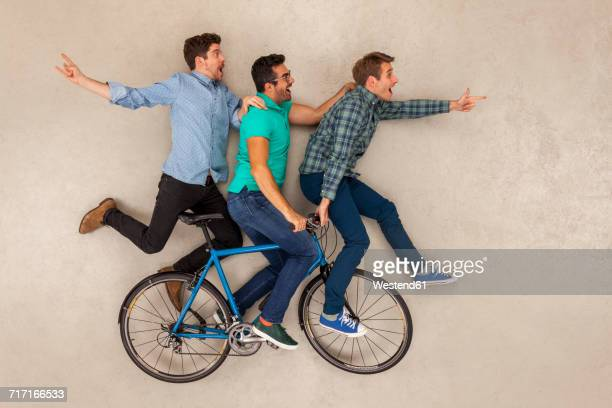 Three friends riding on one bicycle