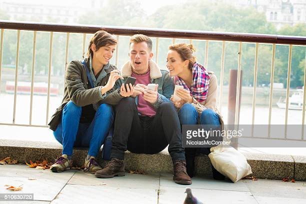 Three friends share media on their mobile phones