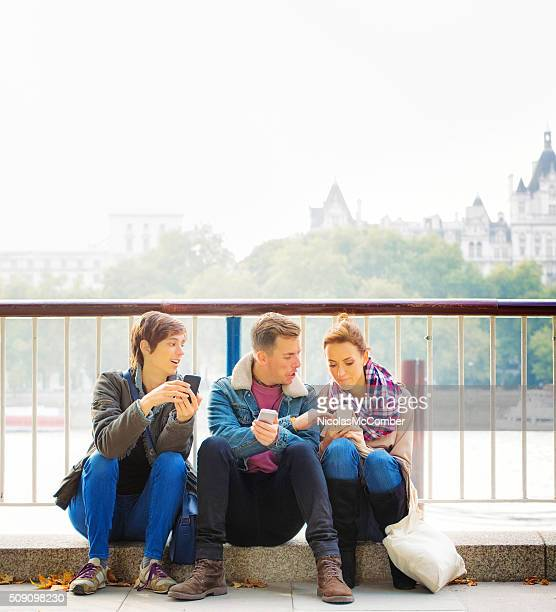 Three friends sharing media on their phones sitting by Thames