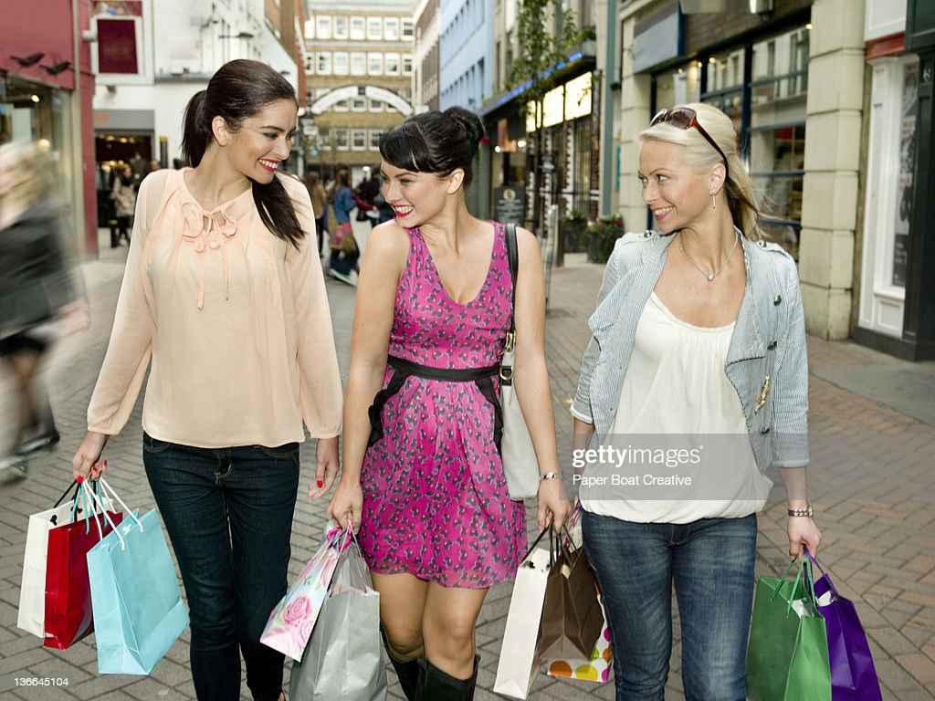 three friends shopping on a London high street : Stock Photo