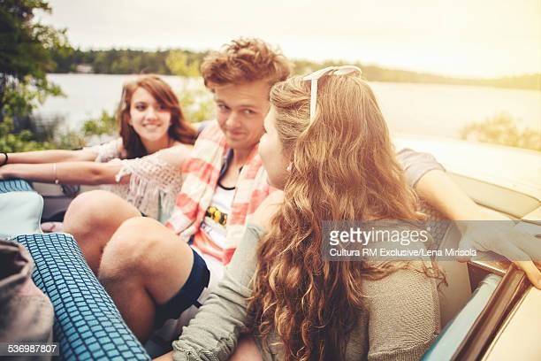 Three friends sitting in convertible