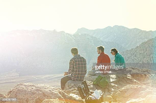 Three friends sitting on mountain top