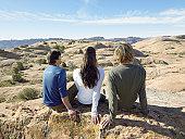 Three friends sitting on rocks, rear view