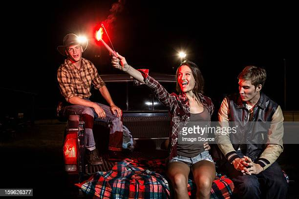 Three friends sitting on tailgate of car at night, girl holding sparkler