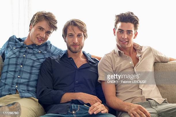 Three friends sitting together on a couch