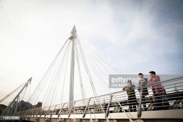 Three friends, standing on bridge, looking at view, Golden Jubilee Footbridge, London, England, UK