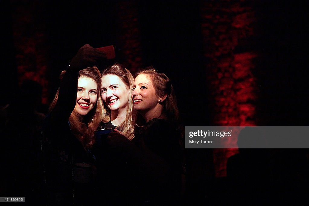 Three friends take a 'selfie' of their 1940s look, complete with Victory Rolls, delicate make-up and bright red lipstick, on the dancefloor of The Blitz Party on February 22, 2014 in London, England. Deep in an East End bunker hundreds of vintage enthusiasts partied like it was 1940 in a range of vintage costumes. They danced to Swing and Jazz music while drinking themed cocktails ordered at the Spitfire Bar, as they embraced the glamour of and popular nostalgia for the era.