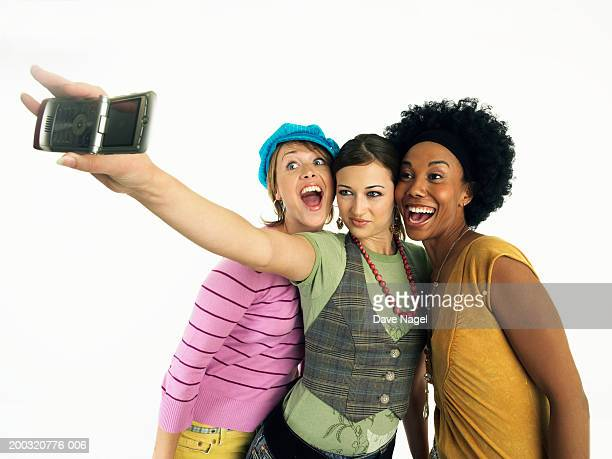 Three friends taking picture with camera phone, smiling