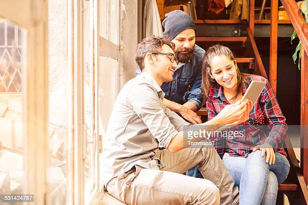 Three friends using tablet sitting on a staircase