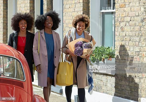 Three friends walk down London street.