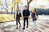 Three friends walk on the street