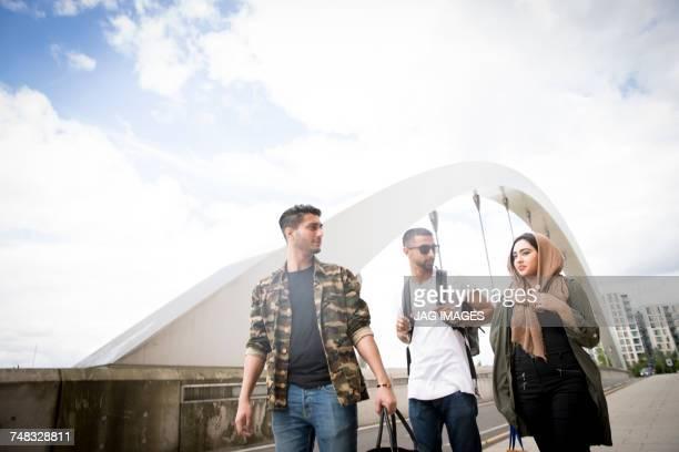 Three friends, walking in street together
