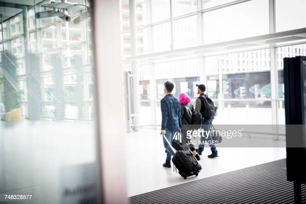 Three friends, walking outdoors, pulling wheeled suitcase, rear view
