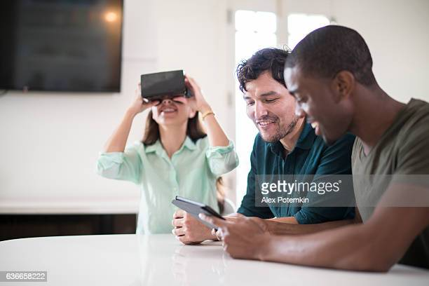 Three friends, white, black and latino, exploring virtual reality