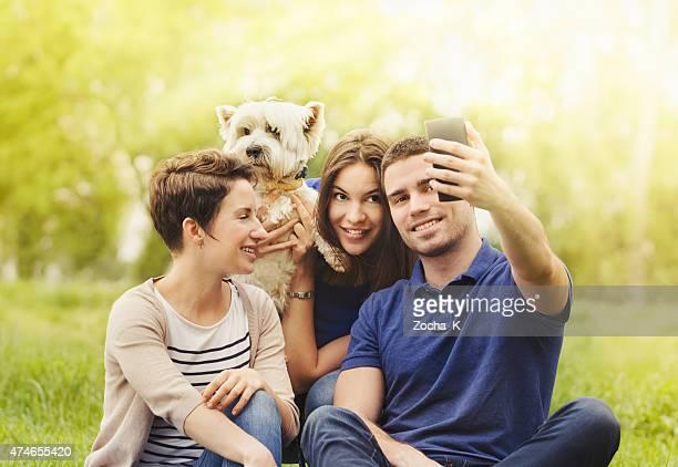 Three friends with dog sitting on grass, joking, taking selfie