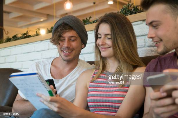 Three friends with notepad and cell phones in a cafe