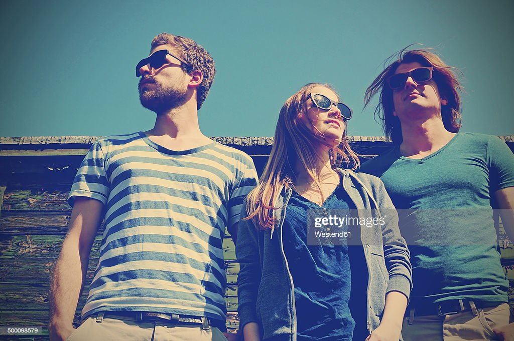 Three friends with sunglasses standing in front of old freight car