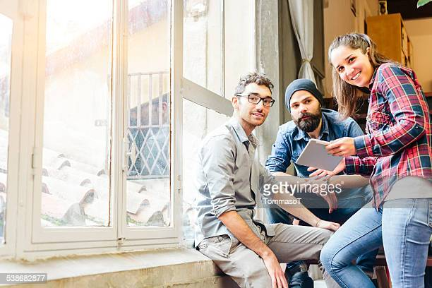 Three friends with tablet on staircase looking at camera