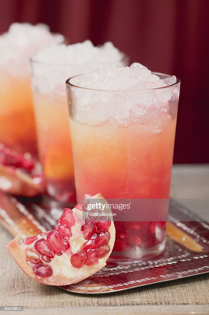 Three fruity drinks with orange juice and pomegranate, close up