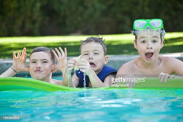 Drei lustige Jungen Floating In einem Swimmingpool