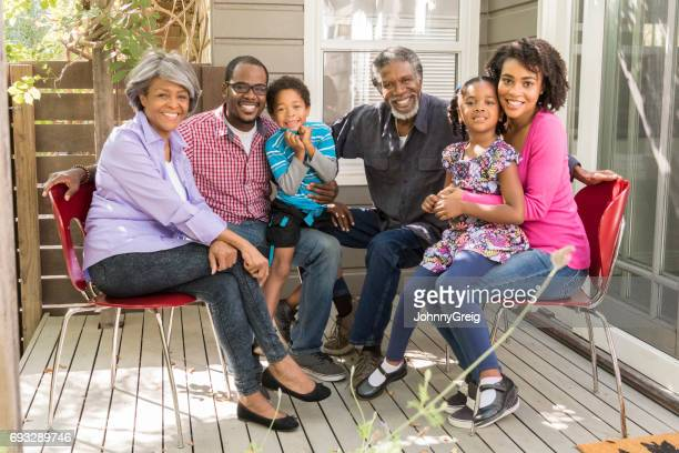 Three generation African American family sitting on patio