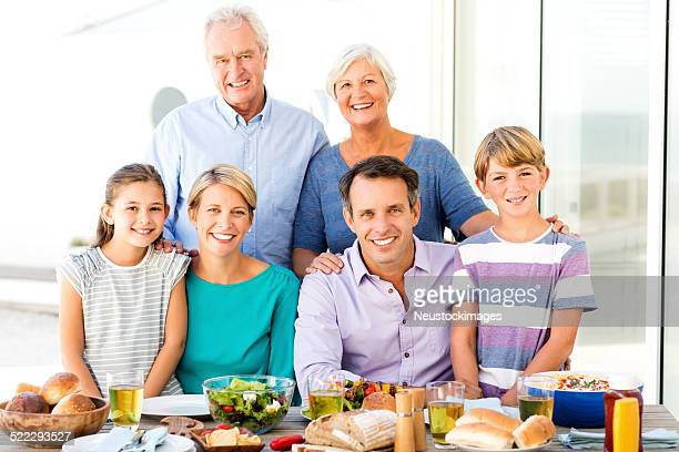 Tres generaciones familia en la mesa de comedor en Porche