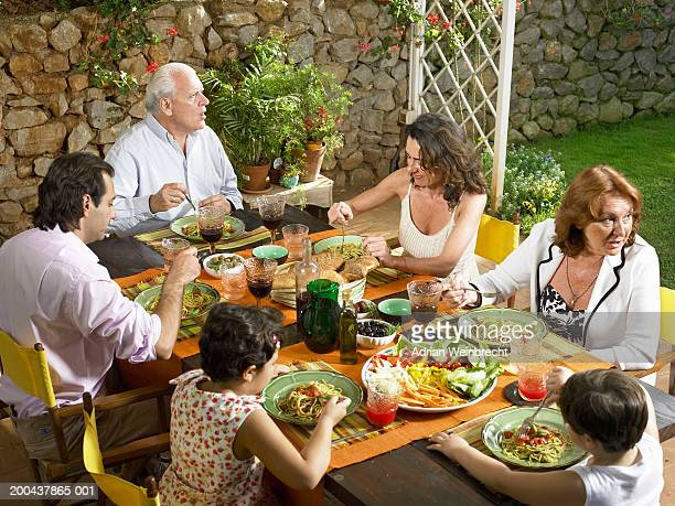 Three generation family at dinner table, outdoors, elevated view
